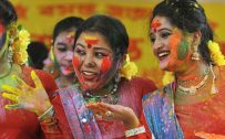 Festival of colors - Holi day in India 2015 - Indian revellers covered with coloured powder dance during Holi festival celebrations